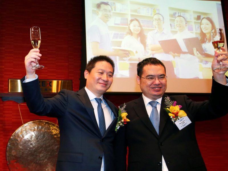 China Literature co-chief executive officers Liang Xiaodong, left, and Wu Wenhui pose during the company's debut at the Hong Kong Exchanges on November 8, 2017. Photo: Reuters/Bobby Yip