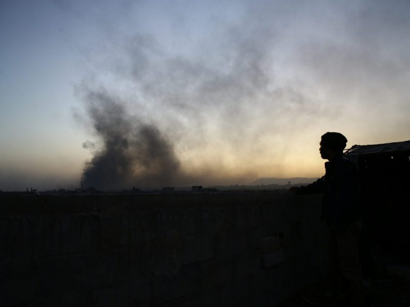 A man watches as smoke rises in the distance, in the Damascus suburb of Ghouta, on November 14, 2017. Photo: Reuters / Bassam Khabieh