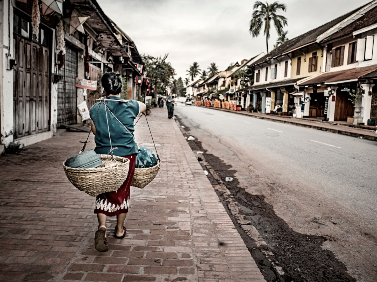 A Lao vendor carries her goods in the main street of Luang Prabang, Laos. Photo: iStock/Getty Images