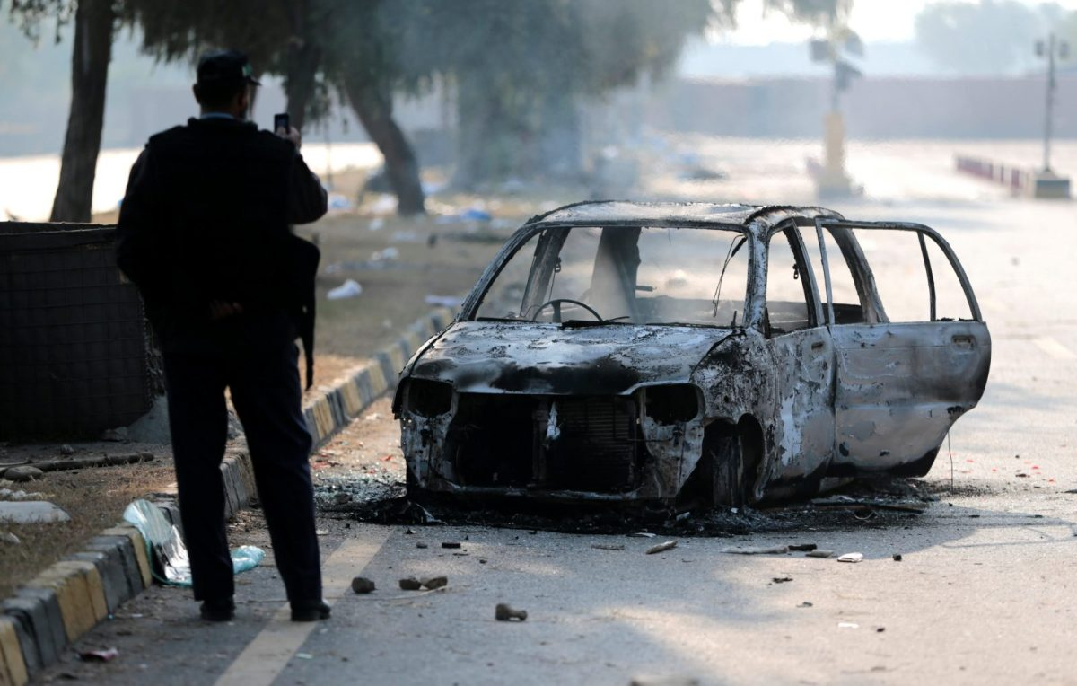 A policeman takes a picture of a car burned during clashes near the Faizabad junction in Islamabad on Sunday. Photo: Reuters