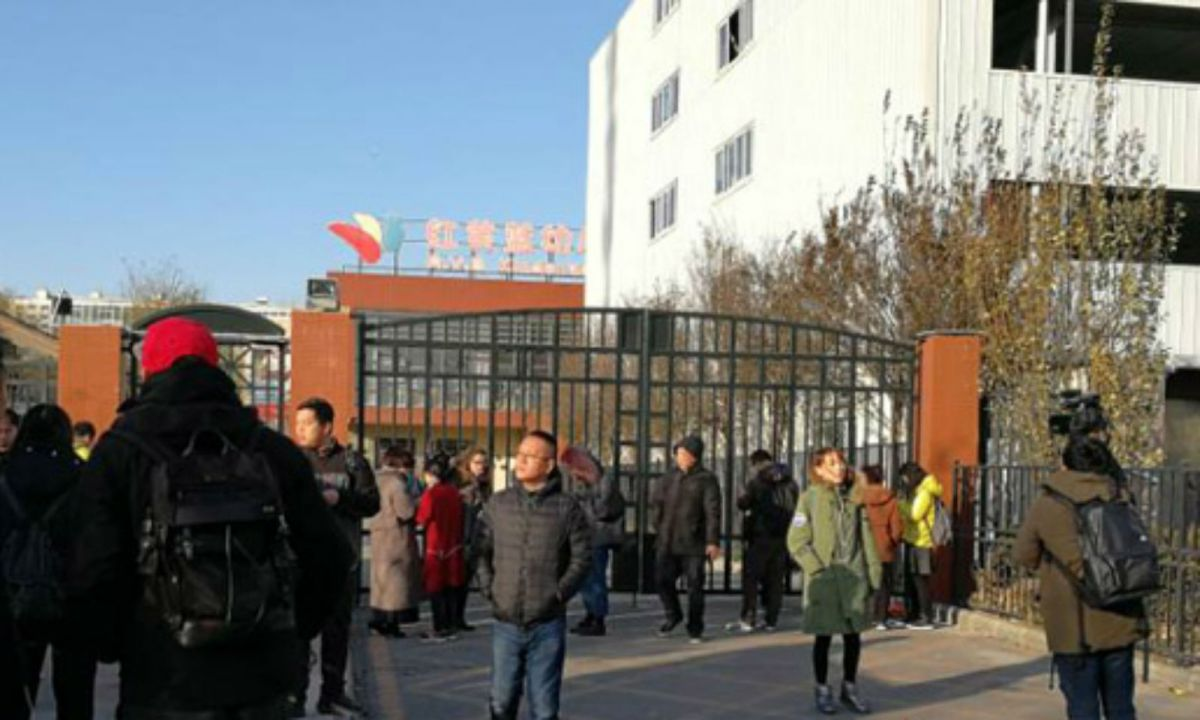 Parents stand outside the gates at the RYB Kindergarten's Xintiandi branch. Photo: bj.people.com.cn
