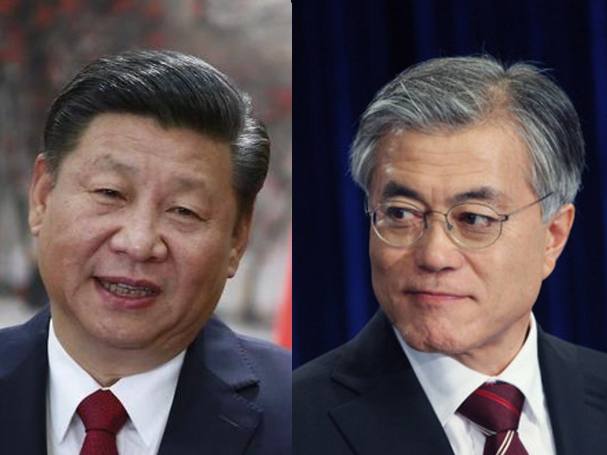 A photo of Chinese President Xi Jinping (L) seen opposite a photo of South Korean President Moon Jae-in.