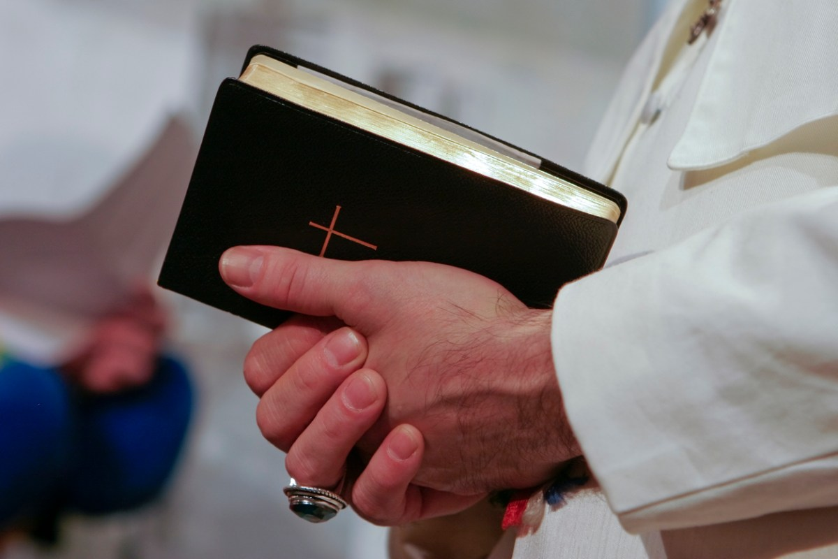 Man in popes garment holding holy bible. Adobe RGB for better color reproduction.Photo: iStock