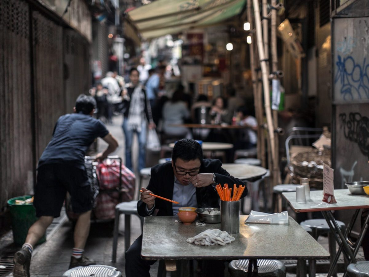 """A man enjoys lunch at a  """"dai pai dong"""" street food stall in Hong Kong's Central district. Who knows whether he is a """"real"""" Hongkonger? Photo: AFP / Anthony Wallace"""