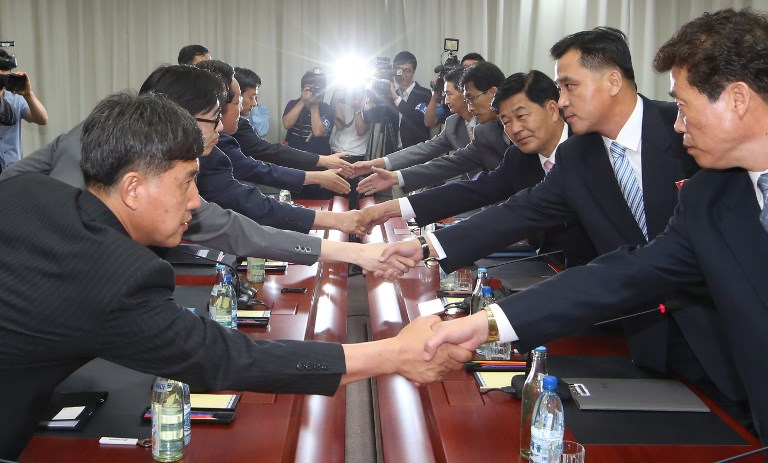 Members of South Korea's Unification Ministry (L) shaking hands with their North Korean counterparts during talks at the joint Kaesong industrial park in 2014. Photo: AFP / South Korean Unification Ministry
