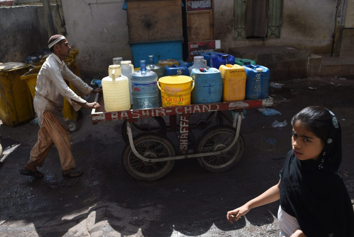 A Pakistani man pushes a cart carrying water in jerry cans in a slum area of Karachi on October 25, 2017. Photo: AFP/Rizwan Tabassum