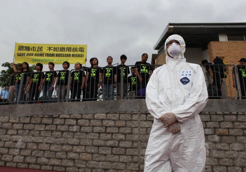 A file photo shows a nuclear safety exercise participant in protective coveralls standing in front of a Greenpeace anti-nuclear protest in Hong Kong. Photo: Caixin