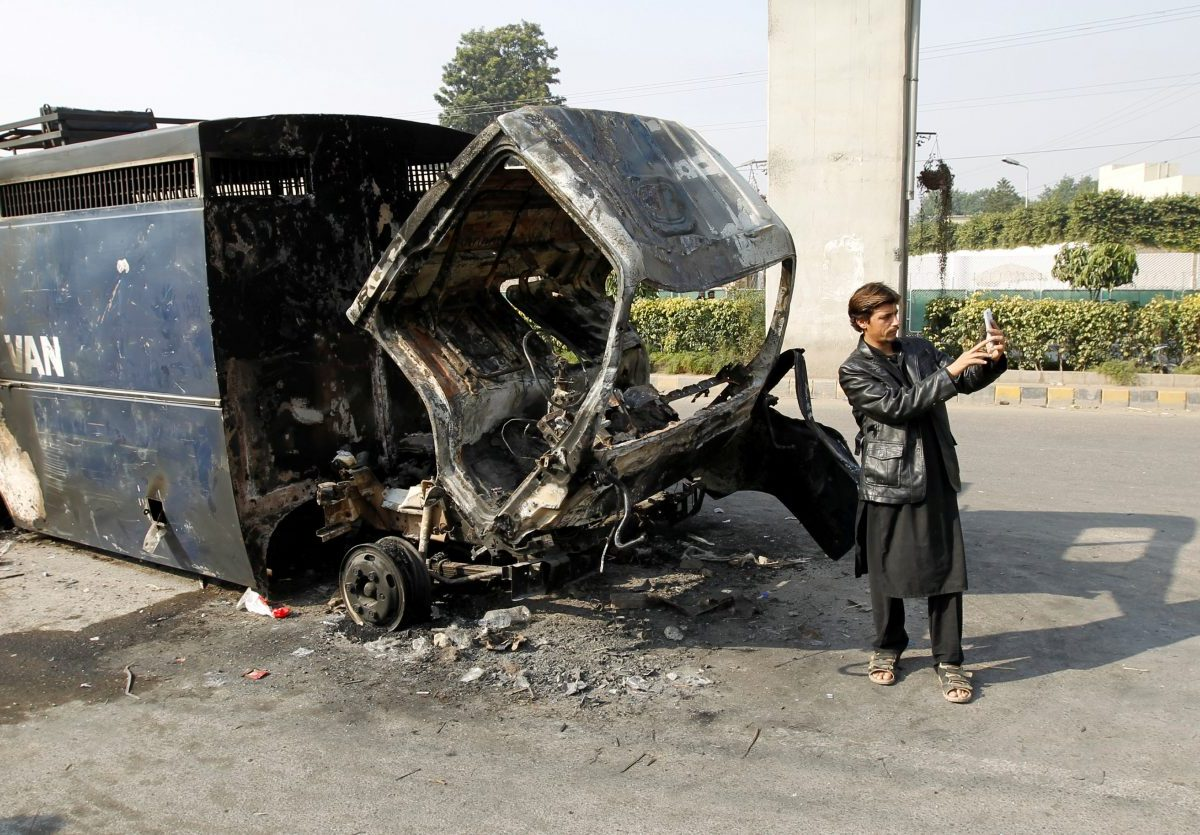 A passerby takes a selfie in front of a police prison van destroyed during clashes with police near the Faizabad junction in Islamabad, Pakistan, on November 26, 2017.  Photo: Reuters / Caren Firouz