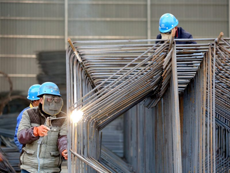 Workers wearing protective masks weld steel bars at a construction site in Huai'an, Jiangsu province. Photo: Reuters