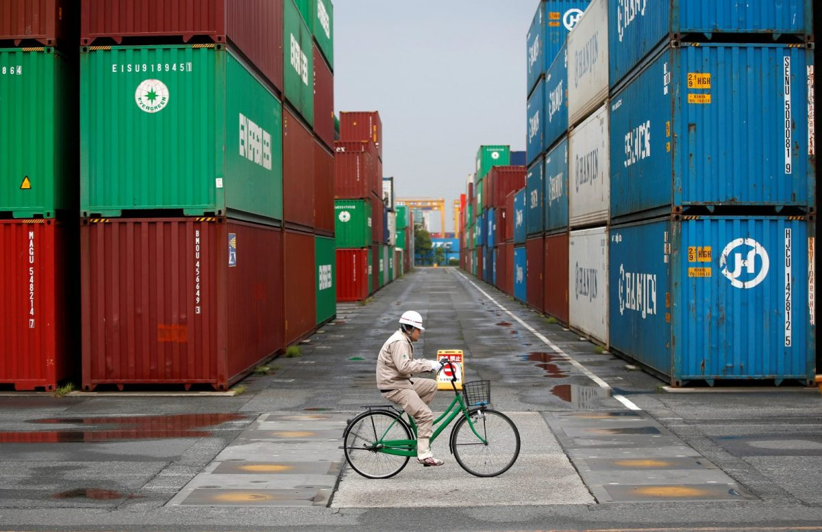 A worker rides a bicycle in a container area at a port in Tokyo. Photo: Reuters / Toru Hanai