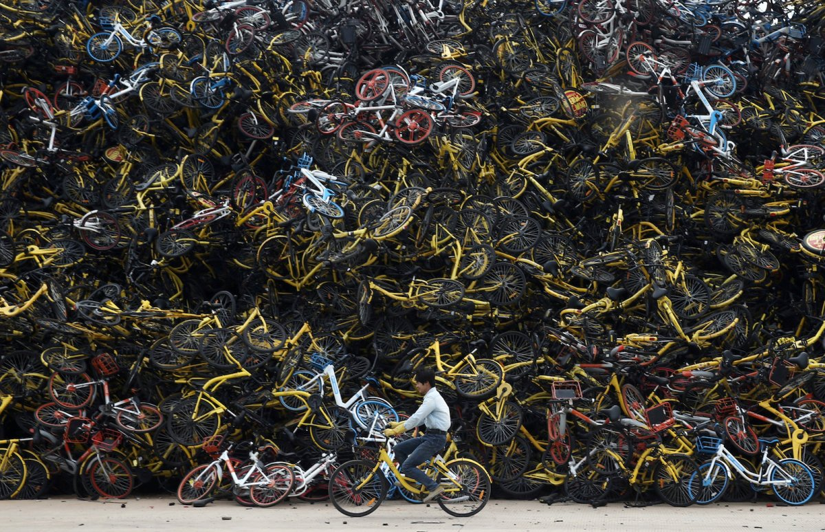 A lone cyclist pedals past discarded bikes in China's Fujian province. Photo: Reuters