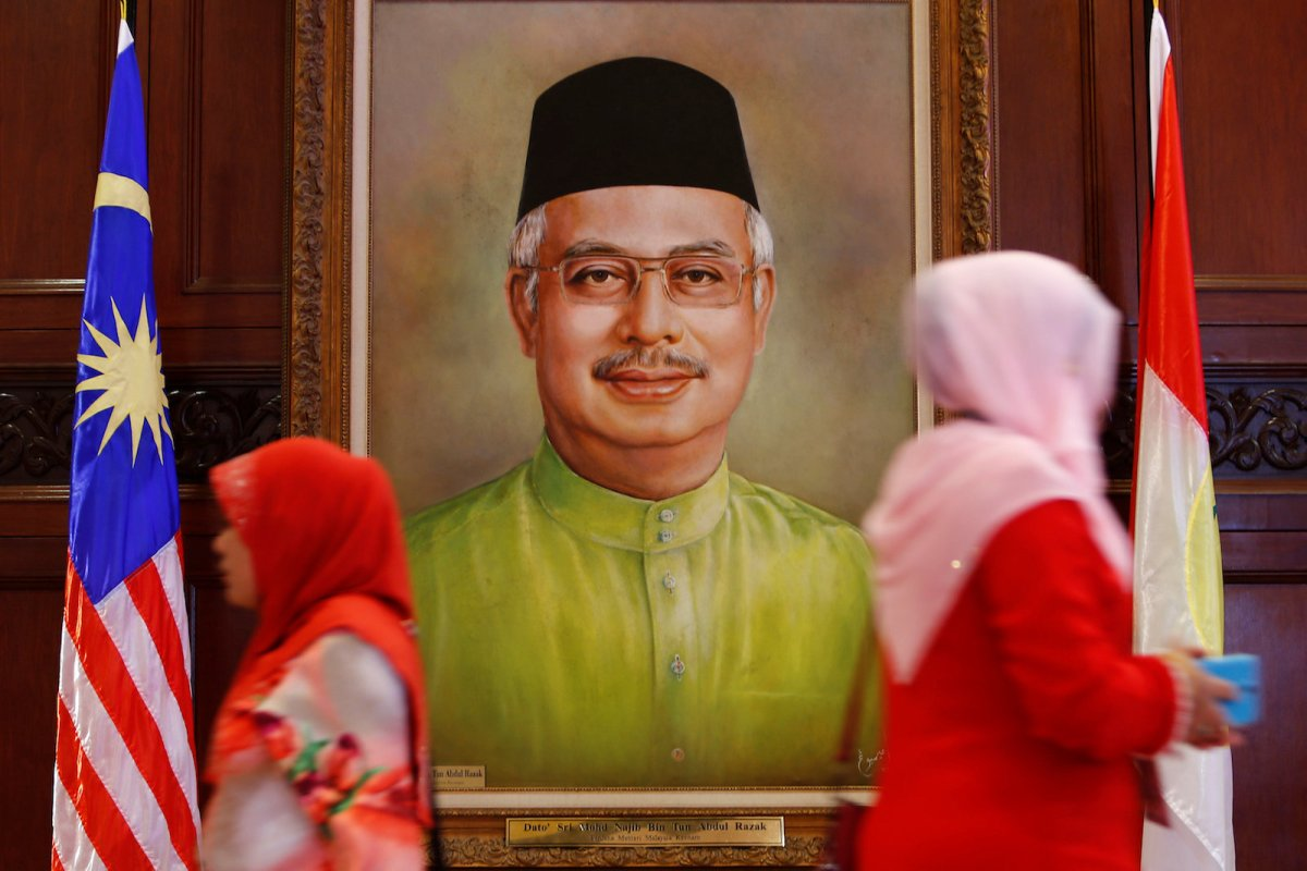 Women walk past a portrait of Malaysia's Prime Minister Najib Razak during the United Malays National Organization (UMNO) general assembly in Kuala Lumpur, Malaysia December 7, 2017. Photo: Reuters/Lai Seng Sin