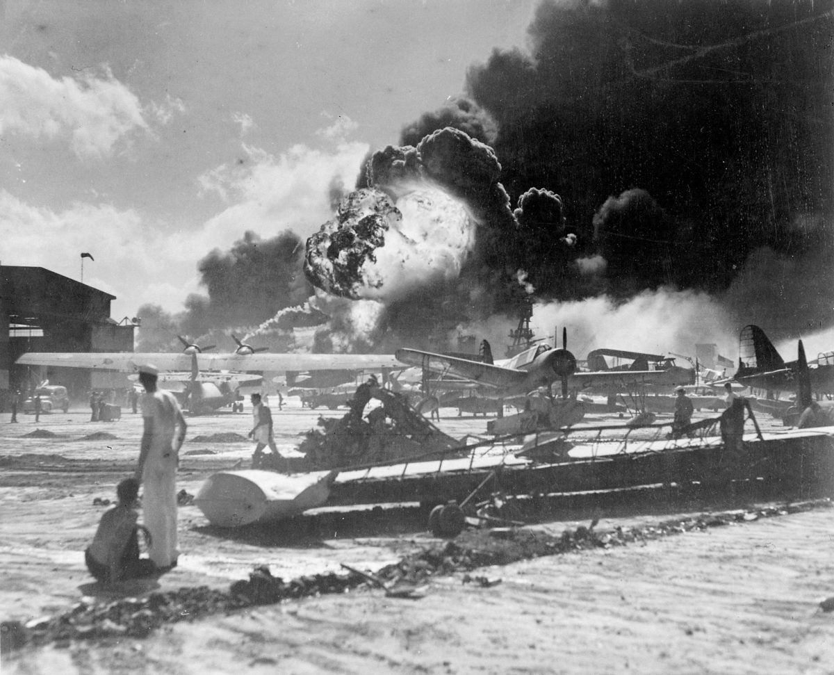 US sailors stand amid wrecked planes at Pearl Harbor after a Japanese attack, watching as USS Shaw explodes in the center background, 7 December 1941. Photo: US Navy, now in the collections of the National Archives.