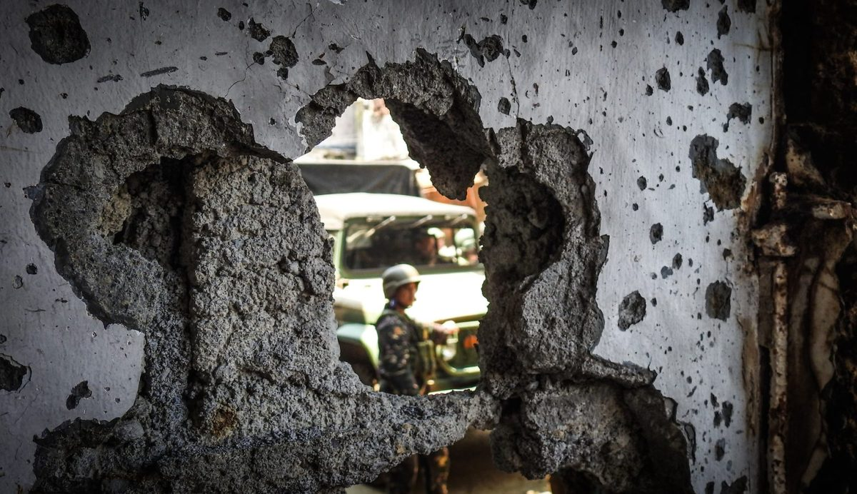 A Philippine soldier is seen through a hole in a wall of a damaged building in the Islamic State sieged city of Marawi on the southern island of Mindanao, August 30, 2017. Photo: AFP/Ferdinandh Cabrera