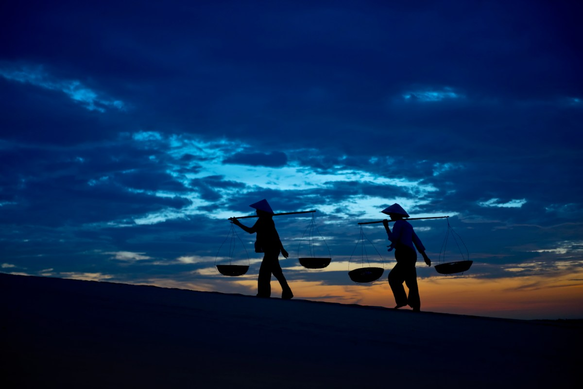 Silhouette of two women carrying wicker baskets trekking across the sand dunes at Bau Trang, Binh Thuan Province in Vietnam at the break of dawn. Photo: iStock/ Getty Images