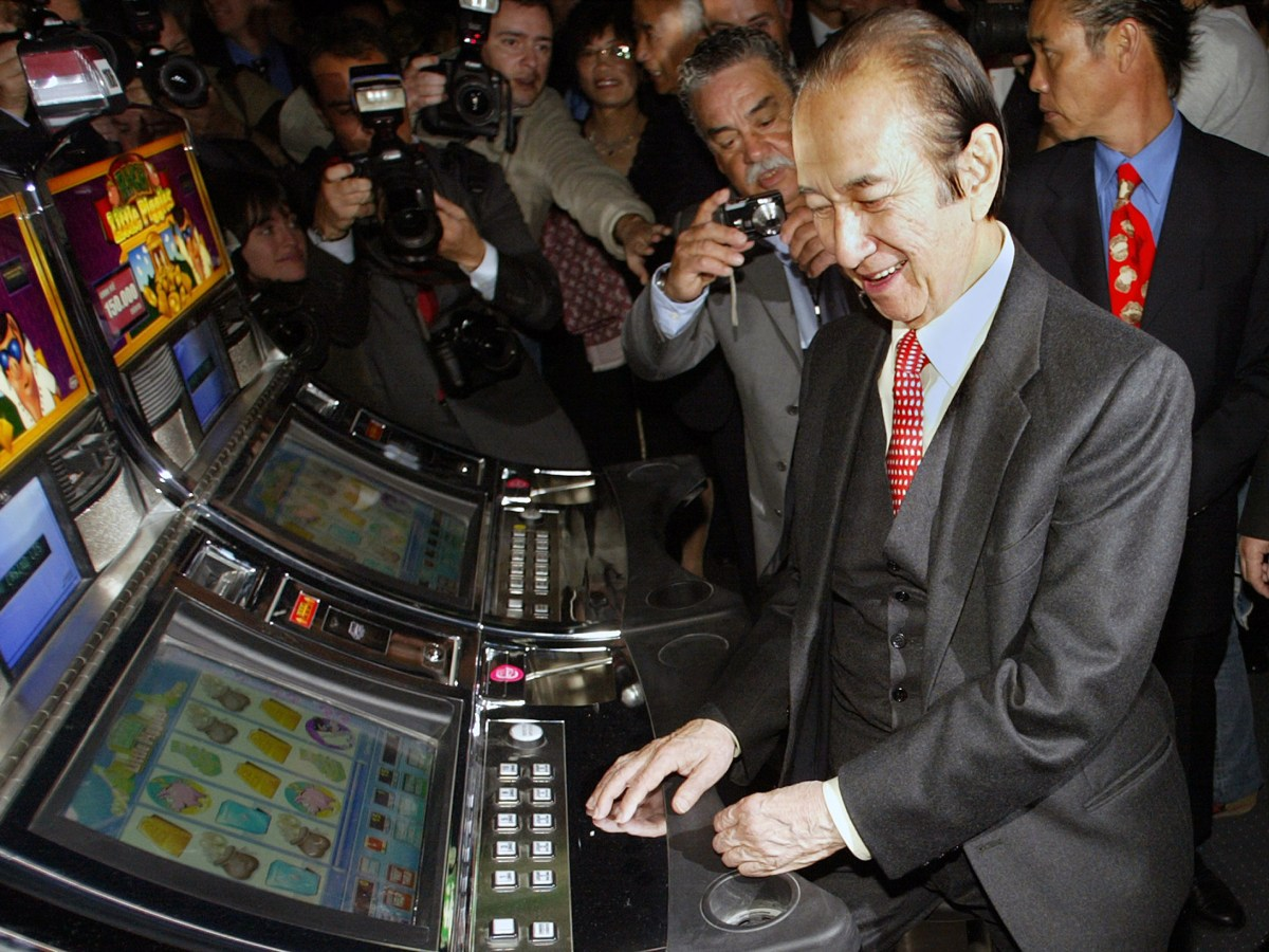 Macau's gambling tycoon Stanley Ho (center) is surrounded by photographers as he operates a slot machine during the opening of a new casino in Lisbon, Portugal, on April 19, 2006. Photo: AFP / Francisco Leong