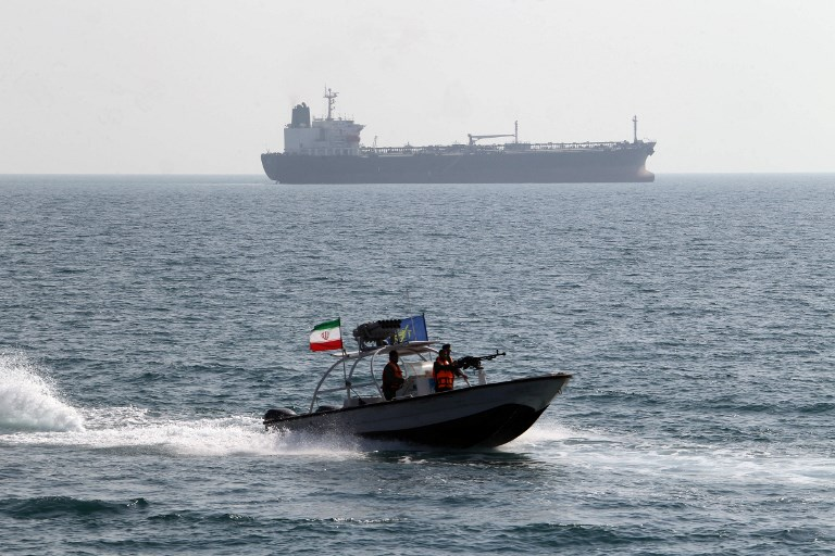 Iranian Revolutionary Guard members drive a speedboat in front of an oil tanker. Photo: AFP/Atta Kenare