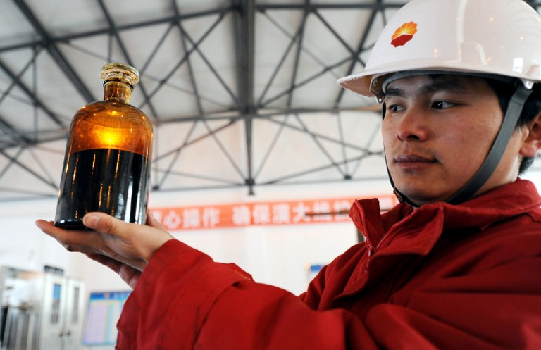 A Chinese worker shows a bottle of crude oil sampled from the oil pipe at the terminal of the China-Russia oil pipeline in Daqing city. Photo: AFP