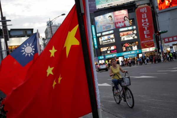 A cyclist rides by Taiwan and Chinese flags displayed during a rally prior to Tsai Ing-wen's presidential inauguration in 2016. Photo: Reuters