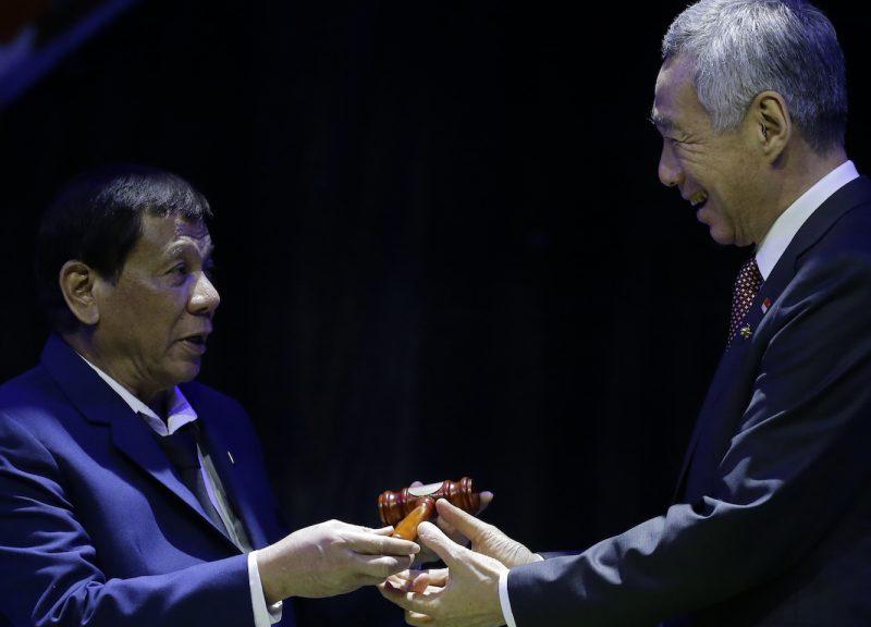 2017年11月14日,在东盟主席团于马尼拉第31届首脑会议的闭幕式期间,菲律宾总统杜特蒂(图左)将木槌交给新加坡总理李显龙。相片:AFP/Aaron Favila/Pool