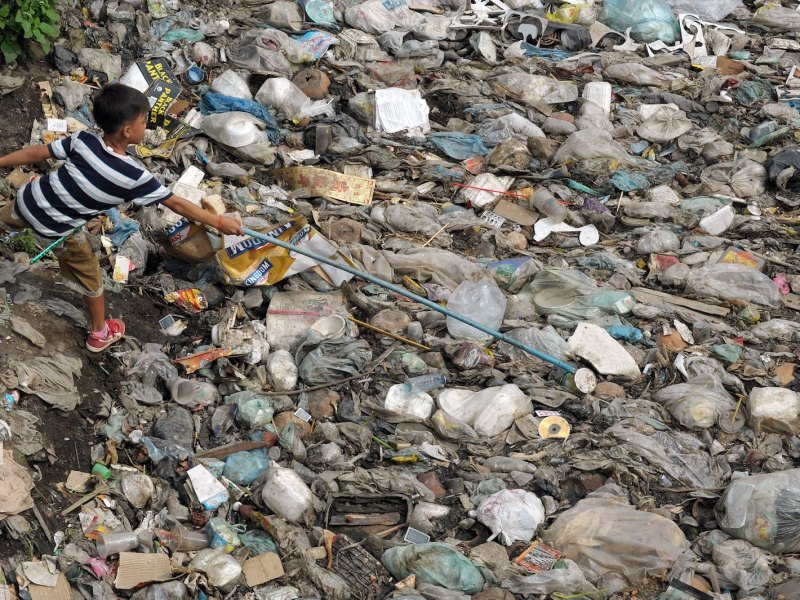 A Cambodian boy (L) tries to pick out a can alongside in a canal filled with waste in Phnom Penh, Cambodia.   Photo: AFP/Tang Chhin Sothy