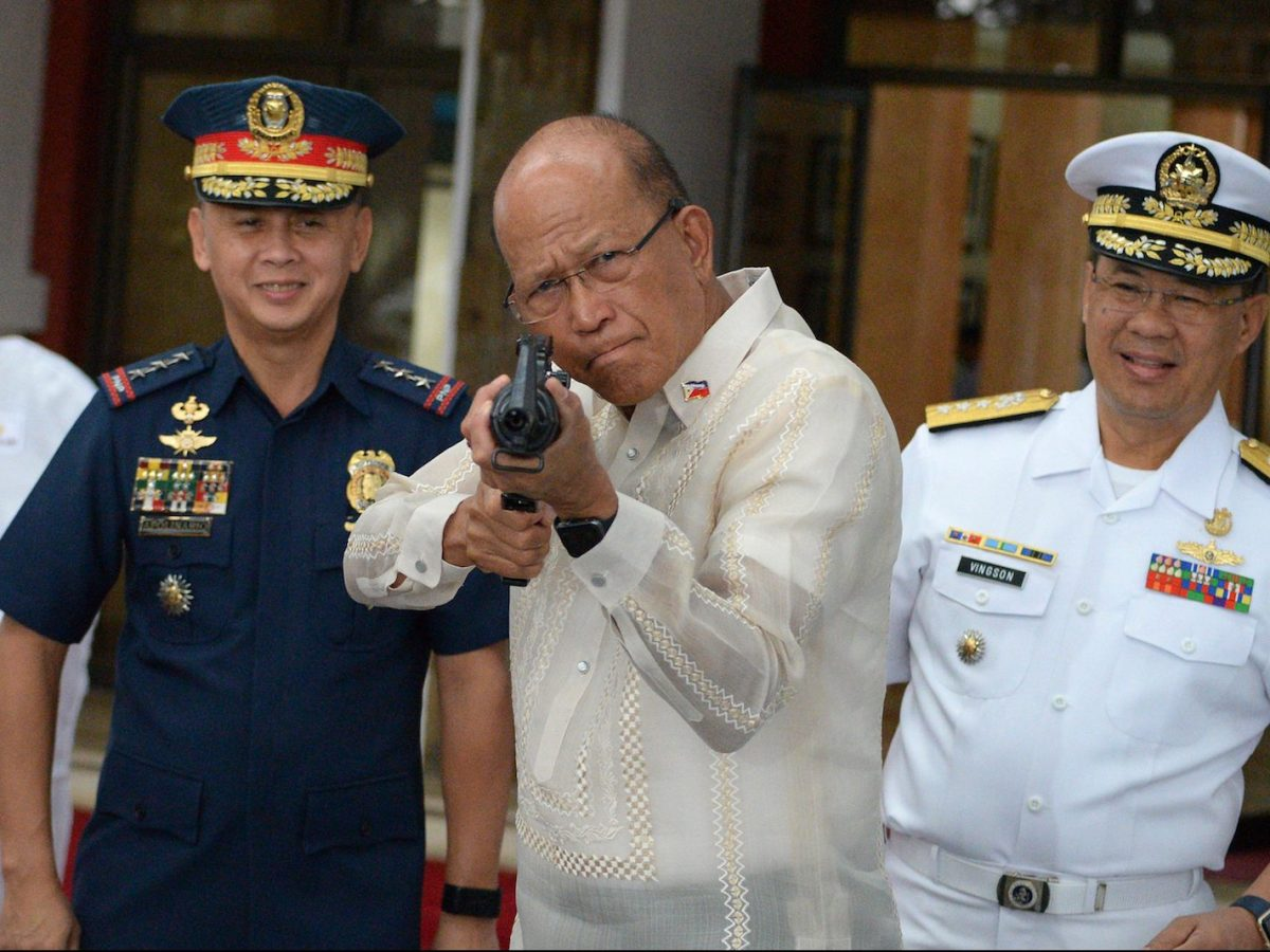 Philippine Defense Secretary Delfin Lorenzana (C) tries a CQ-A5b (M4) rifle donated by the Chinese government during the ceremony at the military headquarters in Manila on October 5, 2017.Photo: AFP/Ted Aljibe