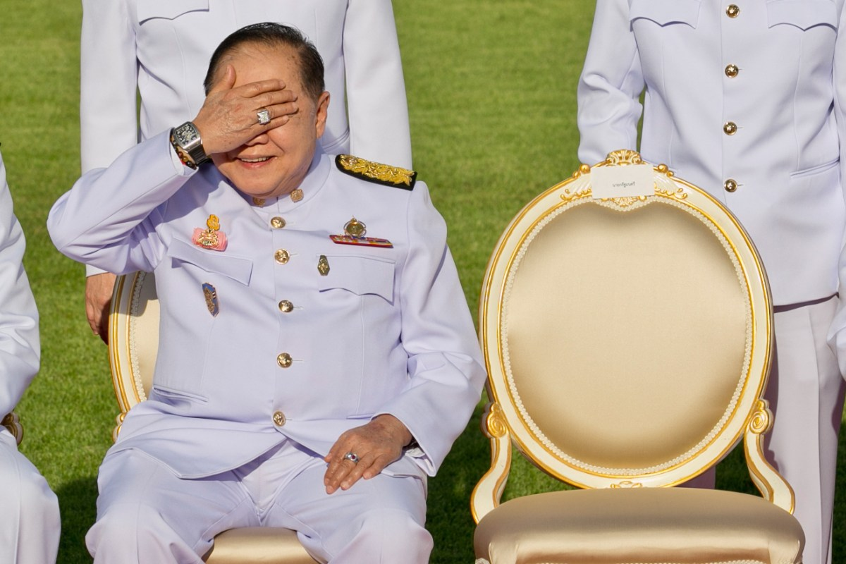 Thailand's junta number two Prawit Wongsuwan covers his eyes, displaying a watch he is wearing, during a photo call with other members of a new cabinet in Bangkok. Photo: AFP/ Krit Phromsakla Na Sakolnakorn