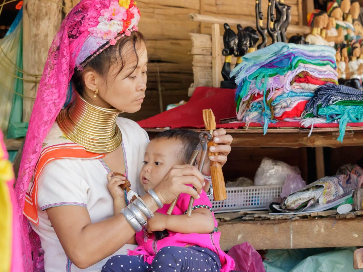 "A ""long neck"" Karen or Kayan woman is seen with a child in a village in Chiang Mai, northern Thailand in this pic from late 2016. She and dozens more fled civil strife in eastern Myanmar over the past 20-30 years. Famous for their traditional golden neck rings they pose for photos with tourists and sell souvenirs. Photo: iStock"