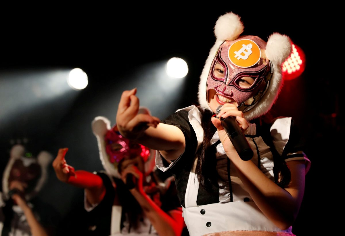 """Members of Japan's """"Virtual Currency Girls"""" pop group, perform in cryptocurrency-themed masks in Tokyo, on January 12. Photo: Reuters / Kim Kyung-Hoon"""