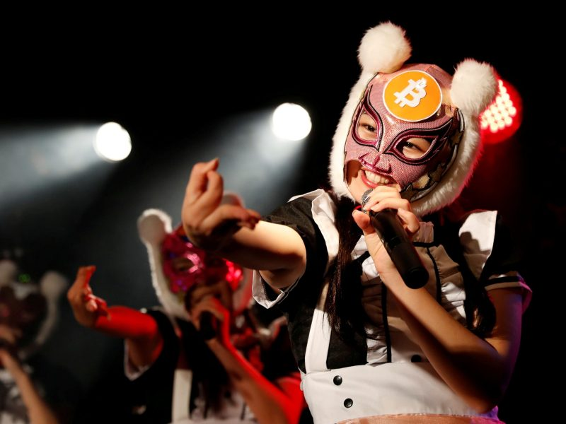 "Members of Japan's ""Virtual Currency Girls"" pop group, perform in cryptocurrency-themed masks in Tokyo, on January 12. Photo: Reuters / Kim Kyung-Hoon"