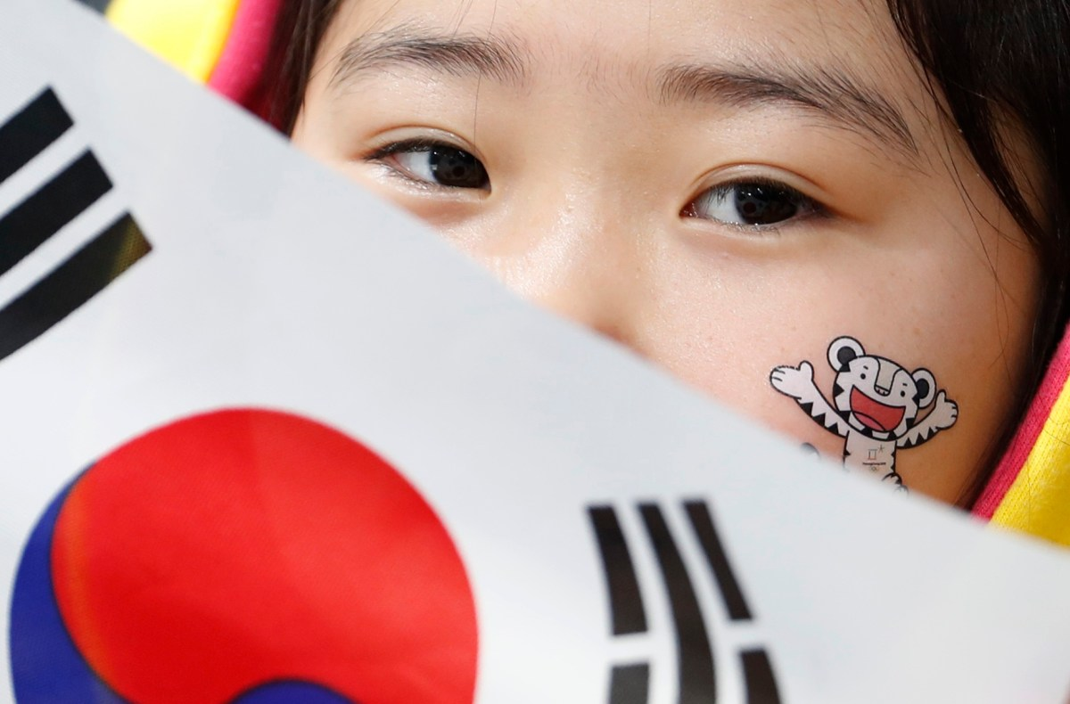 The Olympic mascot, Soohorang, is seen painted on the face of a young spectator. Photo: Reuters / Cathal Mcnaughton