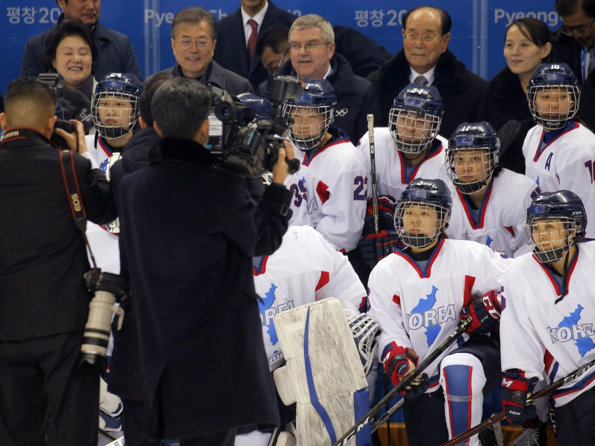 South Korean President Moon Jae-in, International Olympic Committee (IOC) President Thomas Bach, Kim Yong-nam and Kim Yo-Jong pose with the Unified Korean Women's ice hockey team. Photo: Reuters / Brian Snyder