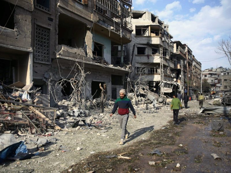 People walk through the damage, after an air raid in the besieged town of Douma, Eastern Ghouta, Damascus, Syria February 23, 2018. Photo: Reuters/Bassam Khabieh