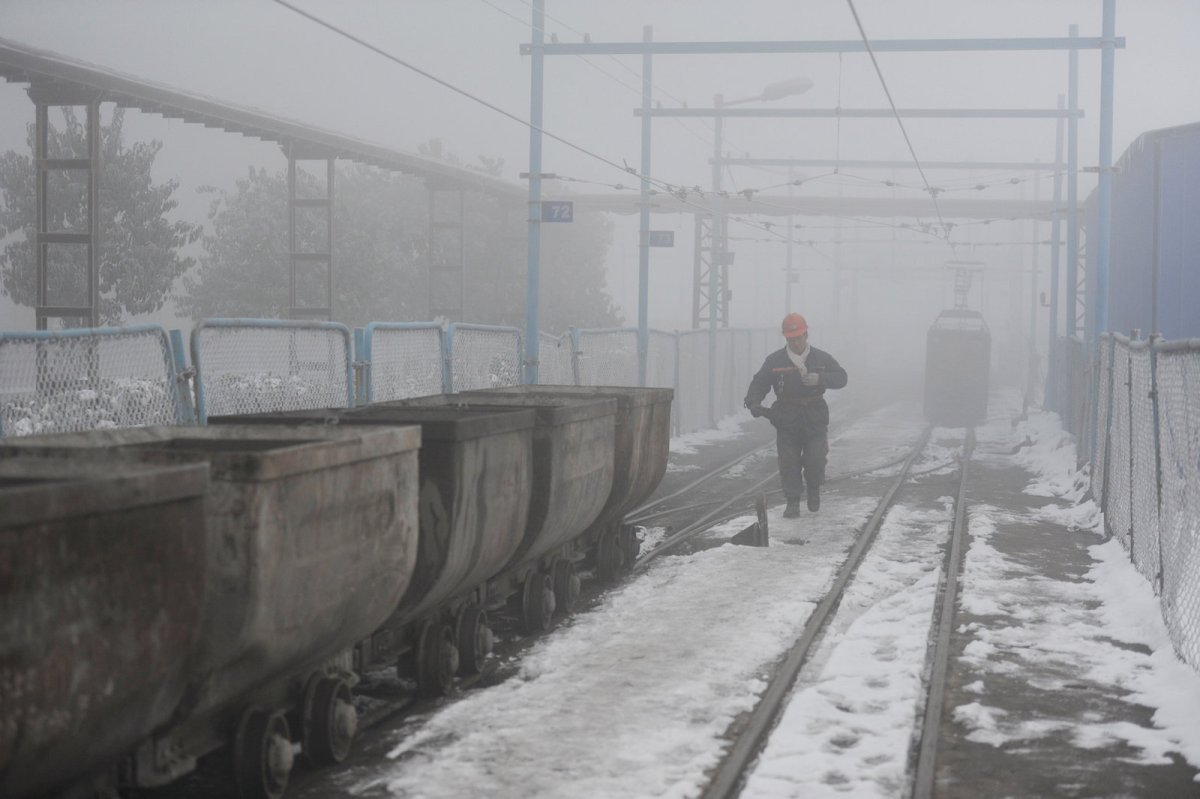 A coal worker walks next to wagons amid smog in Huaibei, Anhui province, China, on January 29, 2018. Photo: Reuters / Stringer / File Photo