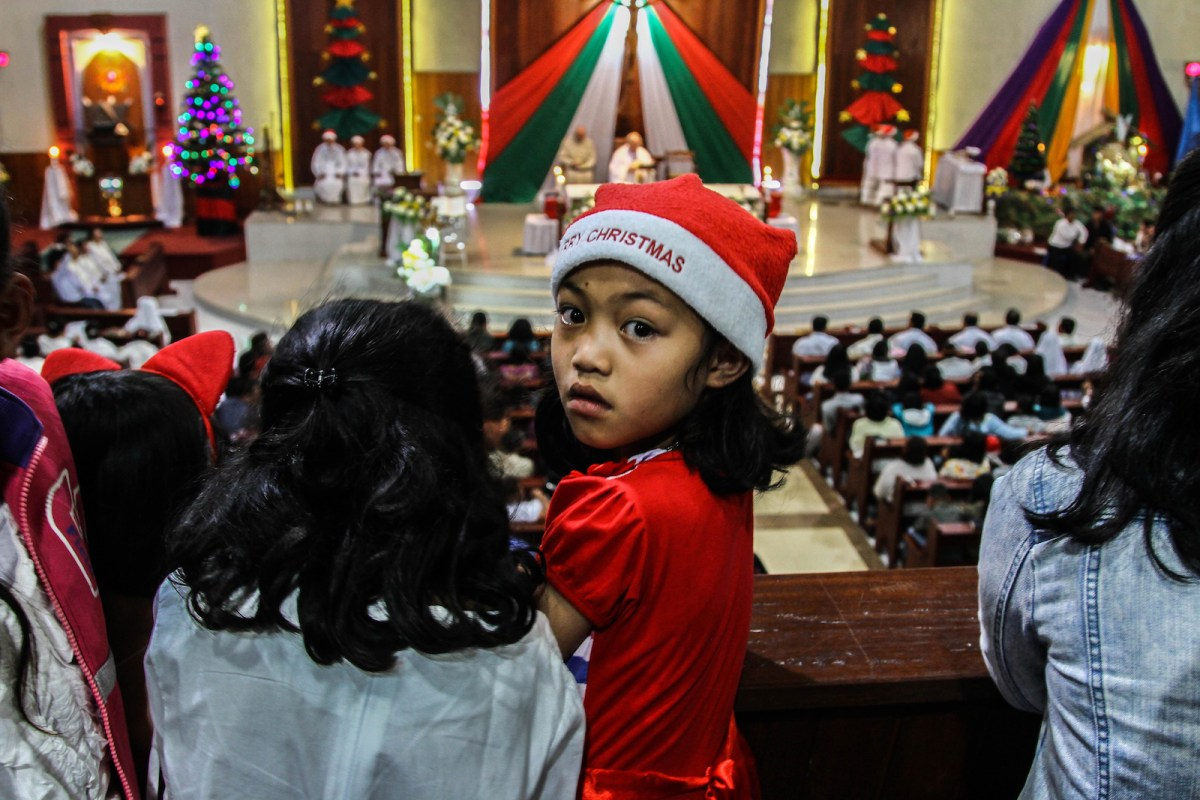 A young Indonesian Catholic looks on as she celebrates Christmas during mass at the Saint Fransiskus Asisi church in Karo, North Sumatra on December 24, 2017. / AFP PHOTO / IVAN DAMANIK