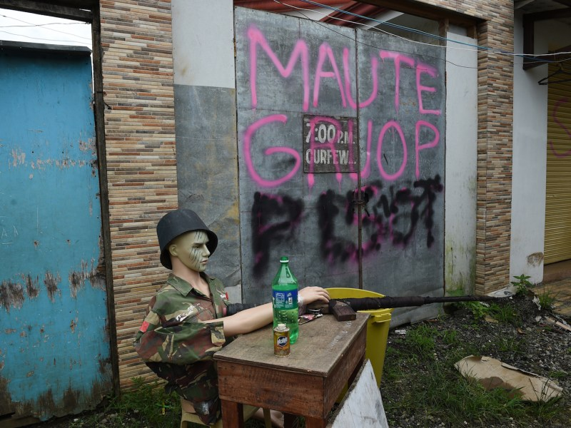 A mannequin dressed in a soldier's uniform and holding a mock rifle is displayed outside a gate near the battle area of Mapandi in Marawi on the southern island of Mindanao on October 19, 2017. Photo: AFP/Ted Aljibe