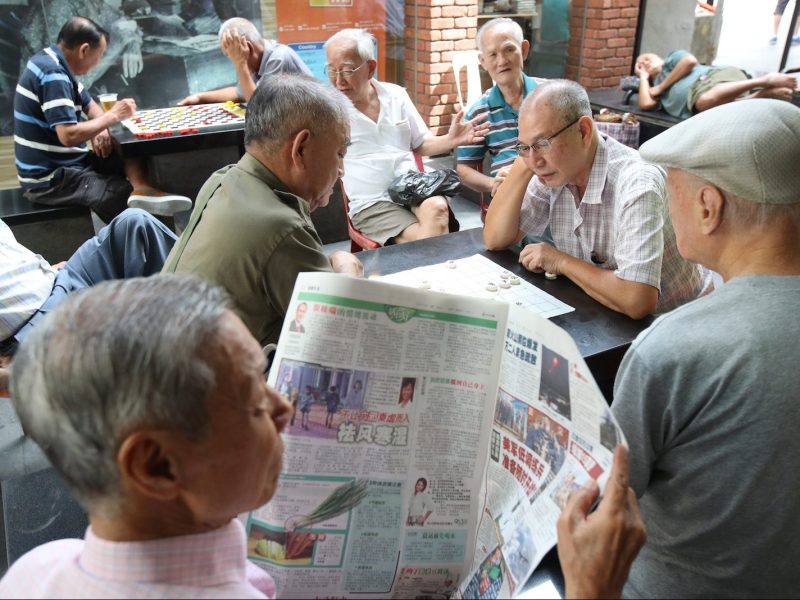 An elderly man reads a newspaper as others play checkers in Singapore, January 16, 2018. Photo: Reuters/Calvin Wong