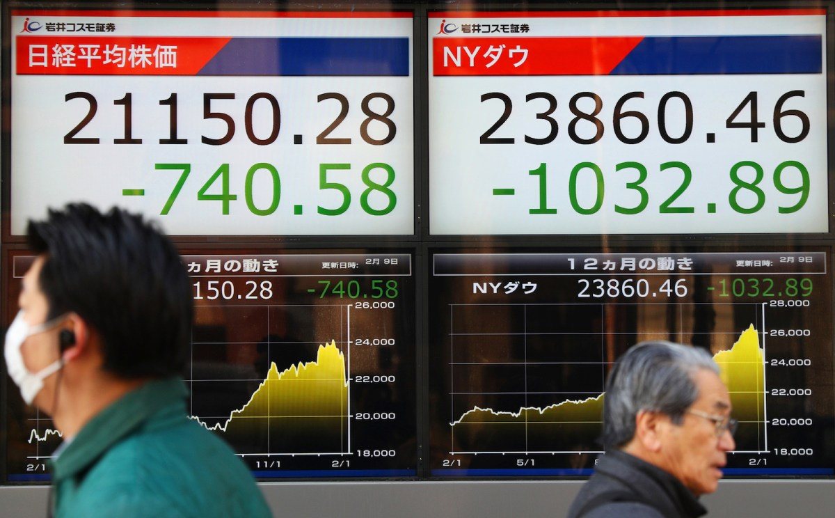 An electric board displays the Nikkei average, left, and New York's  Dow in Tokyo. Photo: AFP / Yomiuri Shimbun