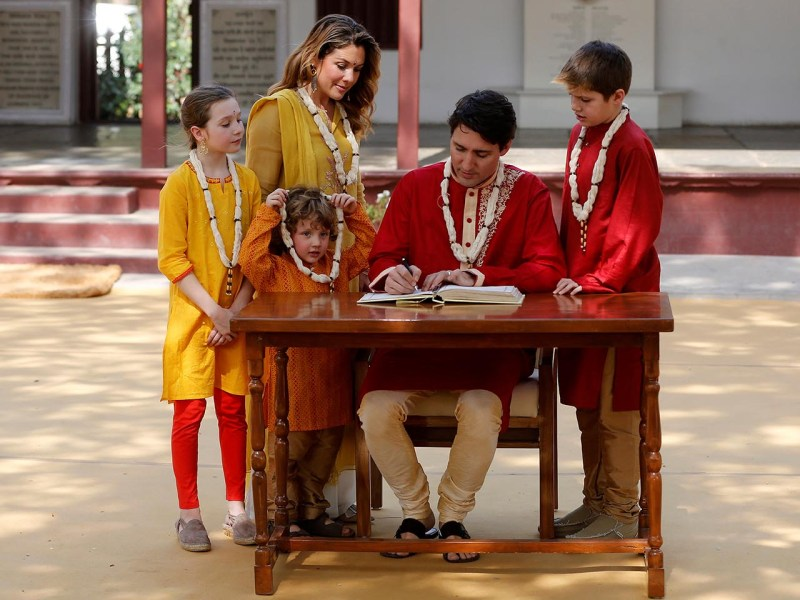 Canadian Prime Minister Justin Trudeau writes a message in the visitor's book at the Gandhi Ashram in Ahmedabad, India on February 19, 2018. HIs wife Sophie Gregoire Trudeau, their daughter Ella Grace and sons Hadrien and Xavier observe. Photo: Reuters/Amit Dave