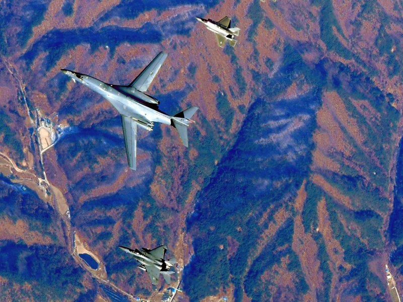 A US Air Force B-1B Lancer bomber is flanked by fighter jets  flying over South Korea. South Korean Defense Ministry handout via AFP