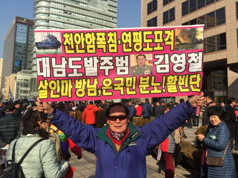 "A conservative protester holds up a sign blaming visiting North Korean delegate Kim Yong-chol, a ""devilish murderer,"" for attacks on a South Korean ship and island in 2010. Photo: Andrew Salmon"