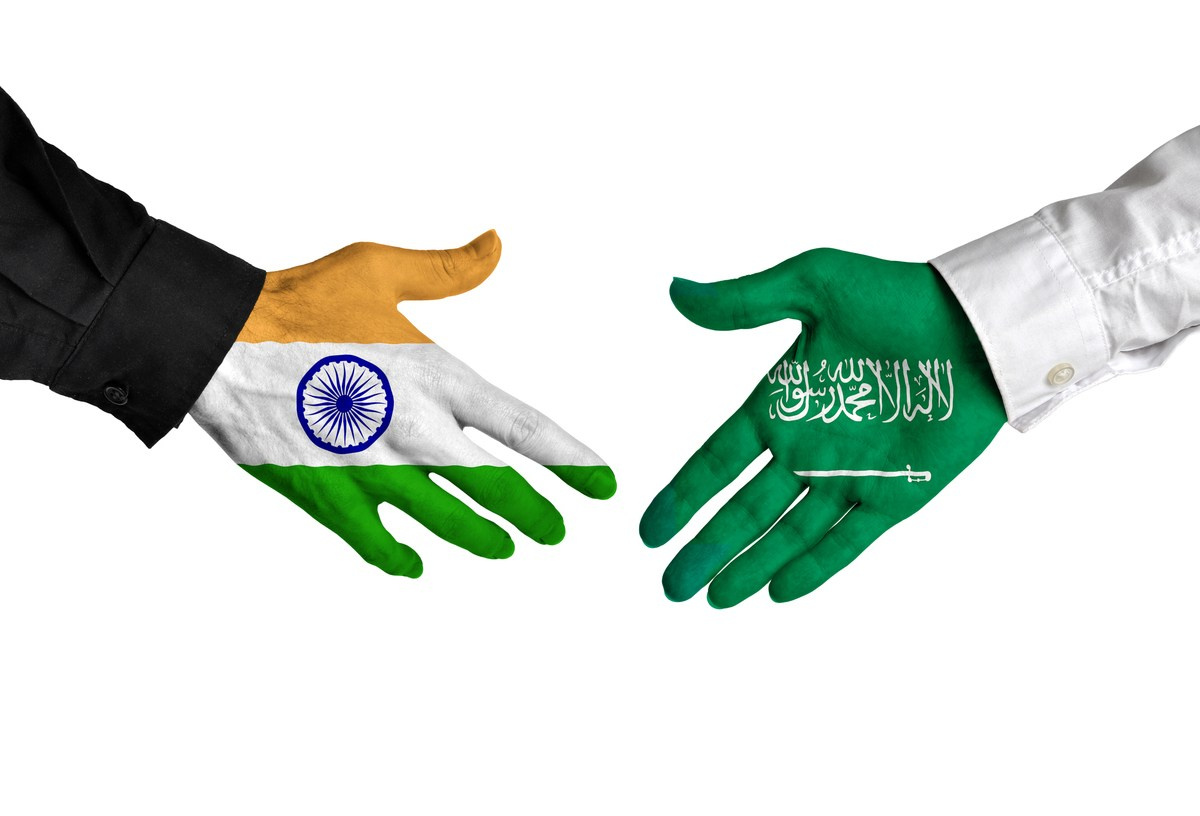 Diplomatic handshake between leaders from India and Saudi Arabia with flag-painted hands. Image: iStock