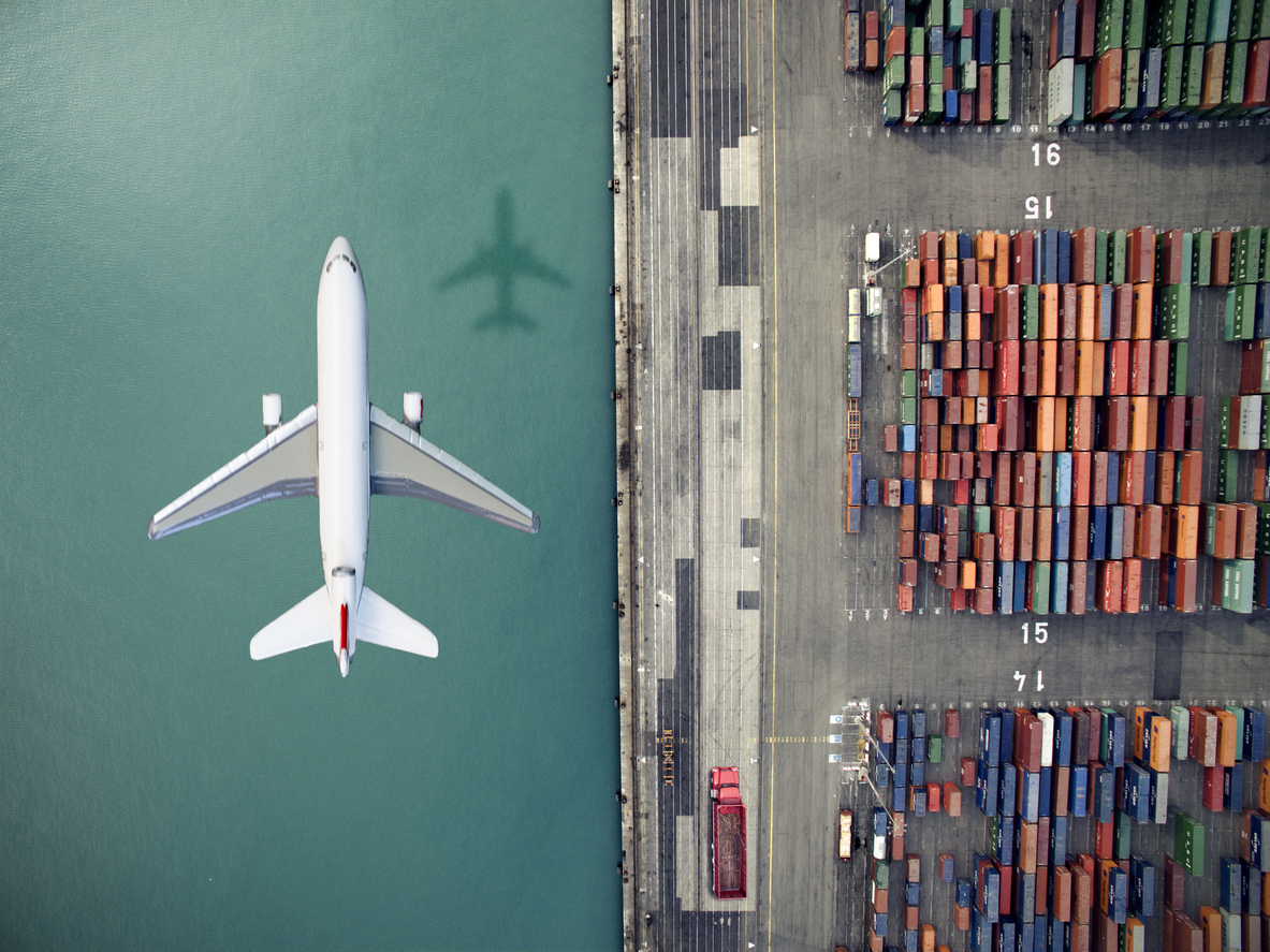 Airplane flying over container port. Photo: iStock