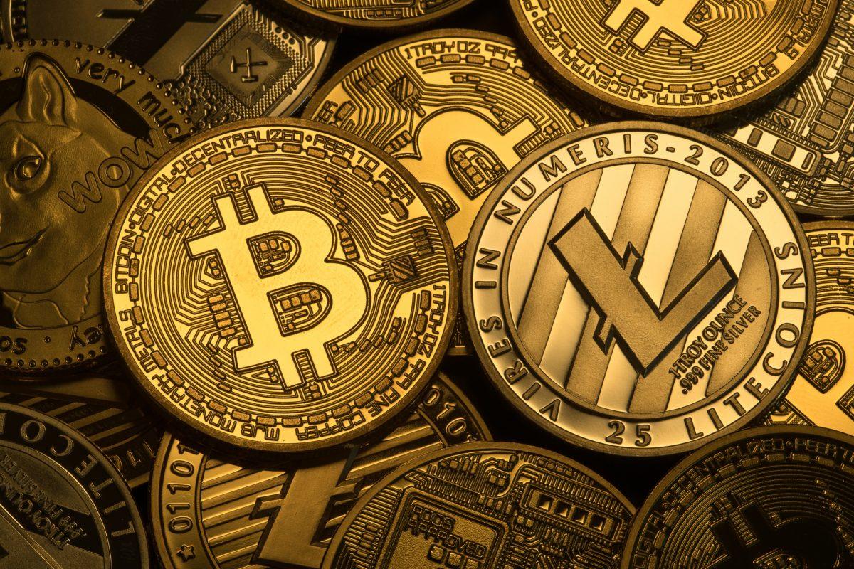 Cryptocyrrencies Bitcoin, Litecoin, Ethereum, dogecoin with trditional money. Photo: iStock