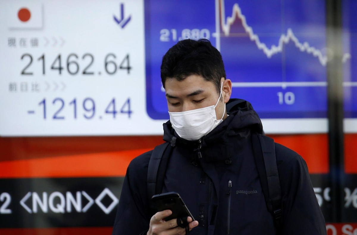 A man checks his mobile phone in front of an electronic board showing Japan's Nikkei average outside a brokerage in Tokyo. Photo: Reuters/Toru Hanai
