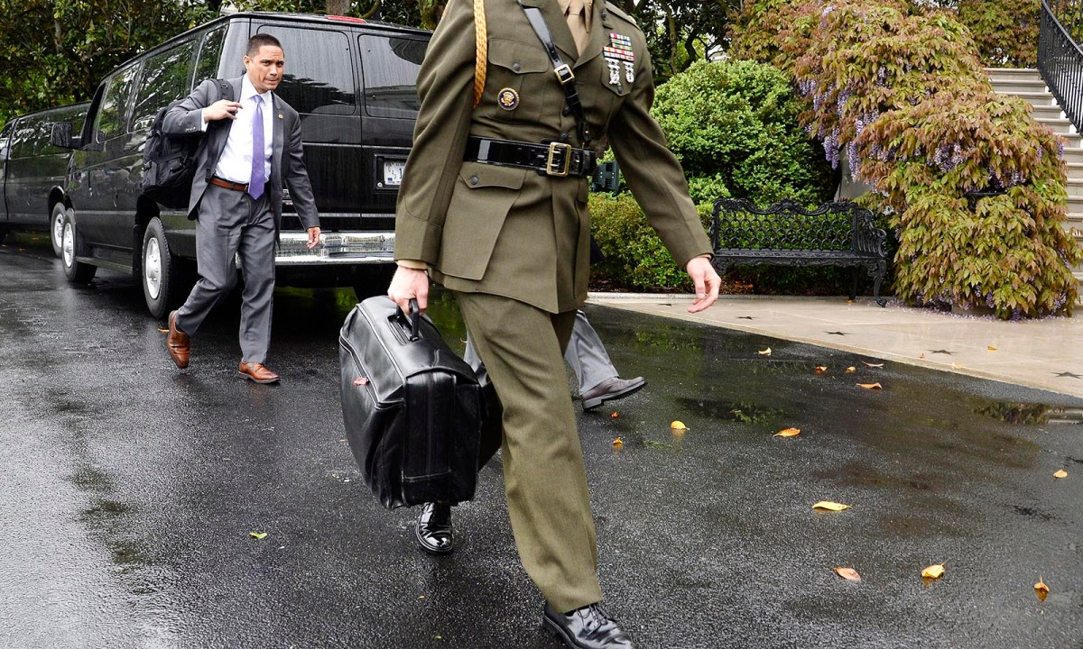 """A US military aide carries the """"nuclear football.""""  Photo: AFP / Olivier Douliery / Pool via CNP"""