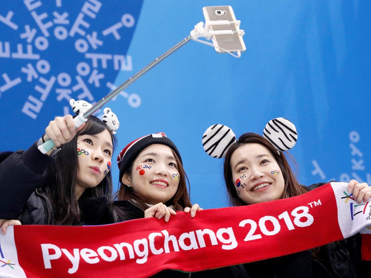 Fans take selfies before the start of Japan's hockey game with Switzerland. Photo: Reuters / Grigory Dukor