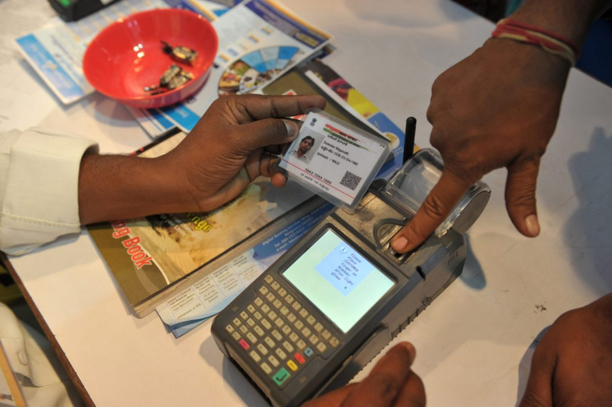 A visitor gives a thumb impression to withdraw money from his bank account with his Aadhaar or Unique Identification (UID) card during an event held to promote digital payment in Hyderabad. Photo: AFP / Noah Seelam