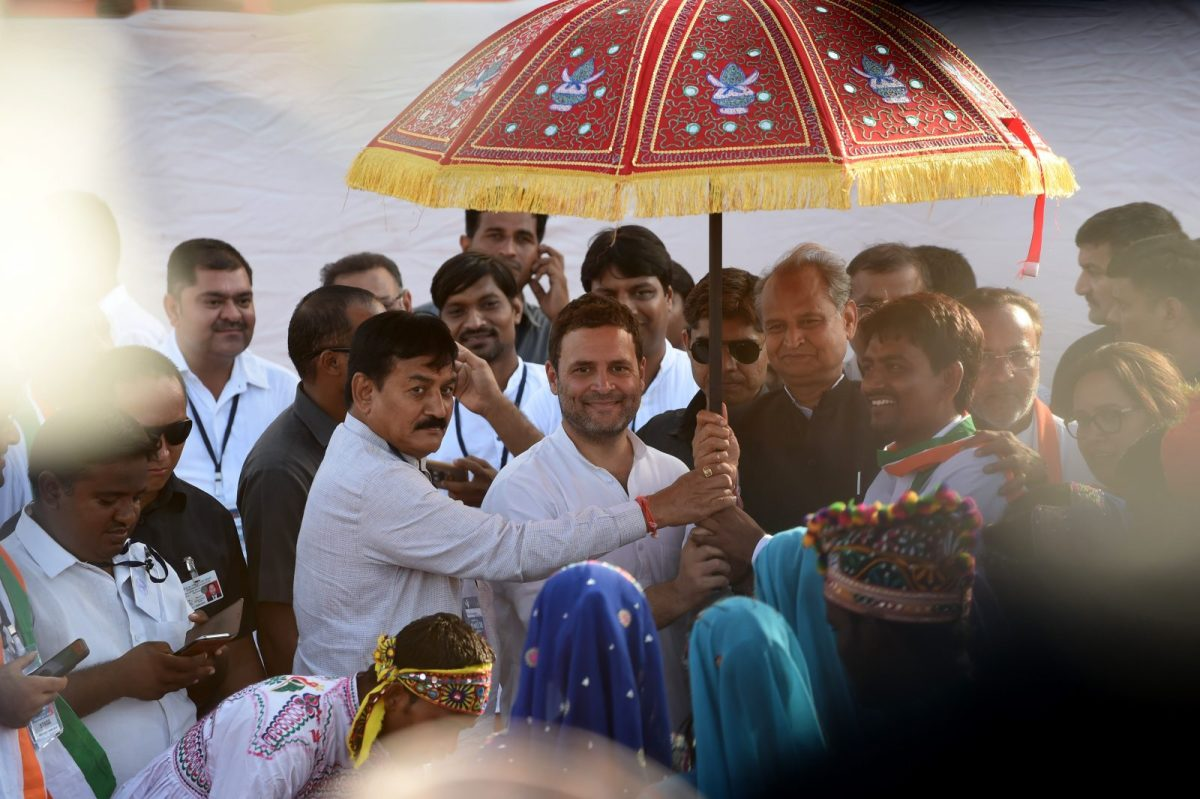Vice President of the Indian National Congress party Rahul Gandhi (C) is seen with Other Backward Class (OBC) leader Alpesh Thakor (R) and President of the Gujarat Congress Committee Bharat Sinh Solanki (L) while holding a traditional umbrella during the 'Navsarjan Gujarat Janadesh' rally in Ahmedabad. Photo: AFP/Sam Panthaky