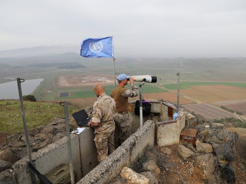 UN soldiers look out on a post at Mount Avital, in the Israeli-occupied Golan Heights near the Israeli-Syrian border on February 10, 2018. Photo: Reuters /  Ammar Awad